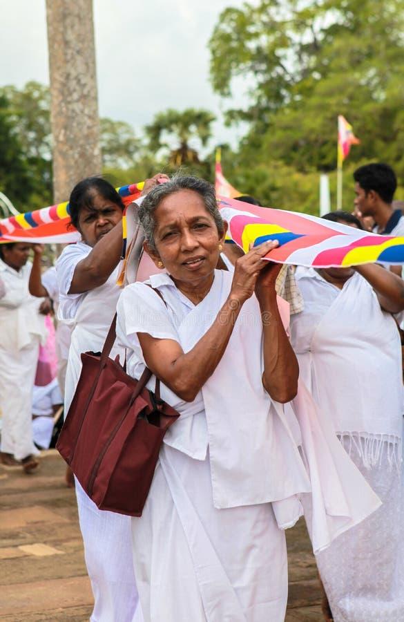 Una donna anziana ai pellegrini in Anuradhapura, Sri Lanka immagini stock