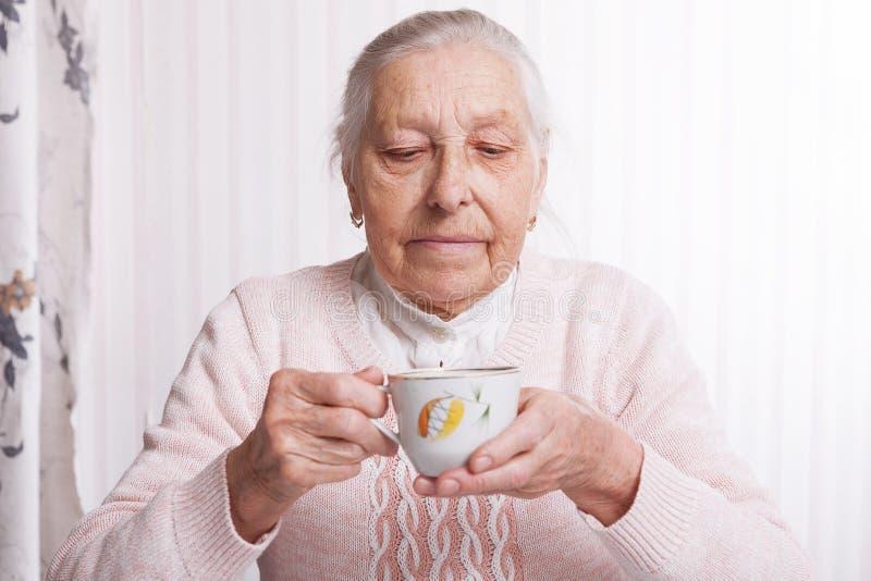 Una donna anziana beve il tè a casa Donna senior che tiene tazza di tè in loro mani al primo piano della tavola fotografie stock
