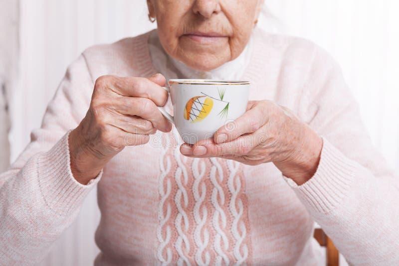 Una donna anziana beve il tè a casa Donna senior che tiene tazza di tè in loro mani al primo piano della tavola immagini stock libere da diritti