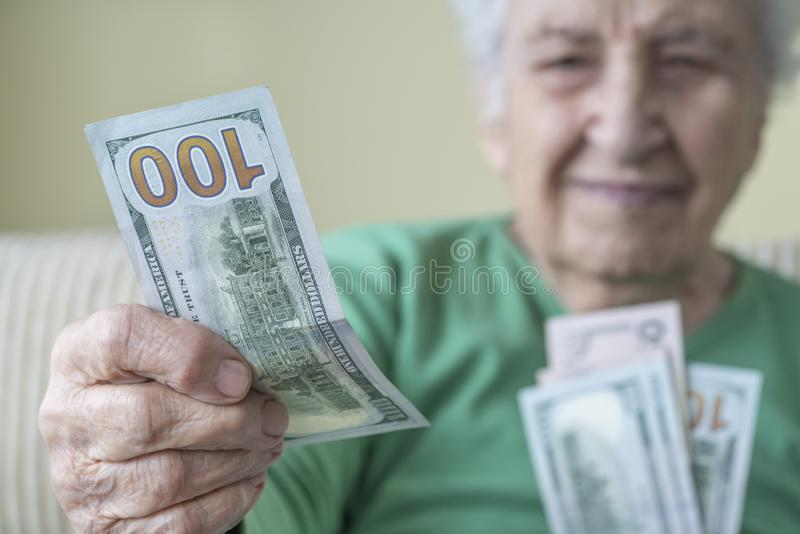 Una donna anziana che dà dollari americani fotografia stock