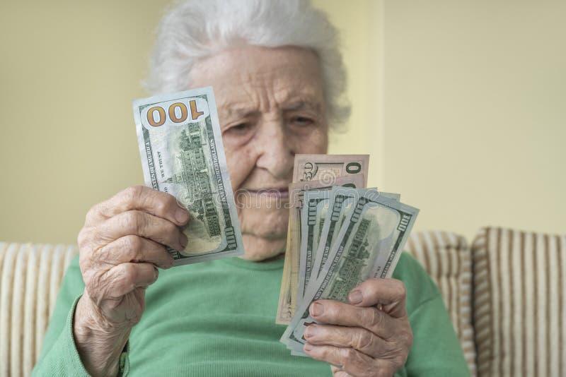Una donna anziana che guarda in mano dollari americani fotografia stock