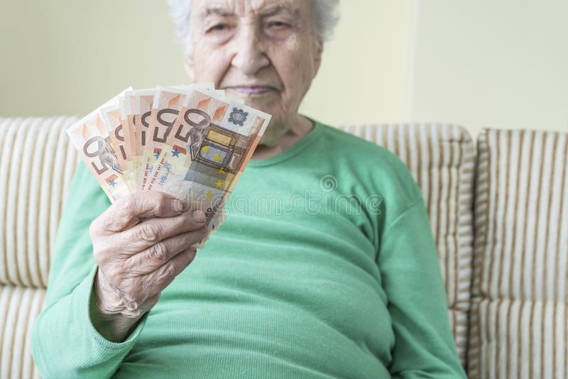 Una donna anziana che guarda in mano le banconote in euro fotografia stock libera da diritti