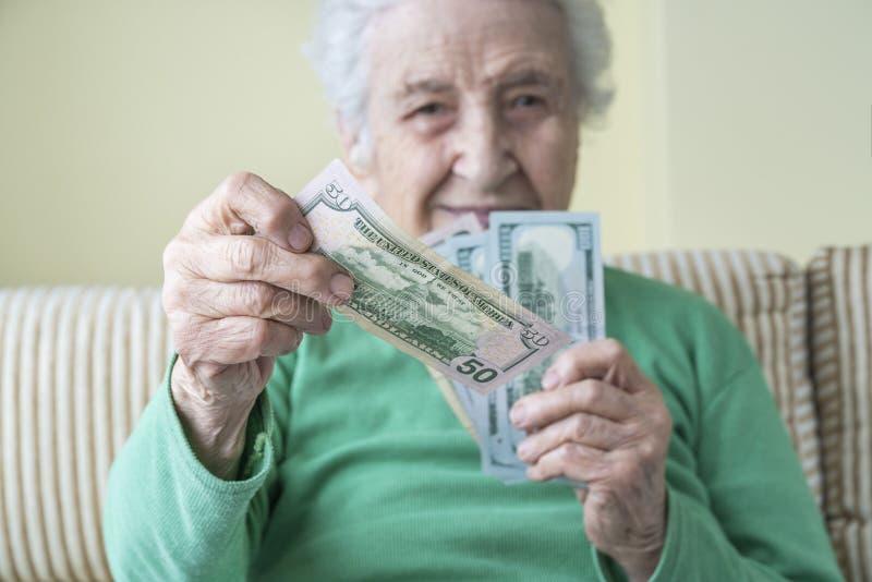 Una donna anziana che regge e dà dollari americani immagini stock libere da diritti