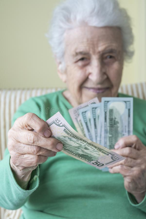 Una donna anziana che regge e dà dollari americani fotografie stock