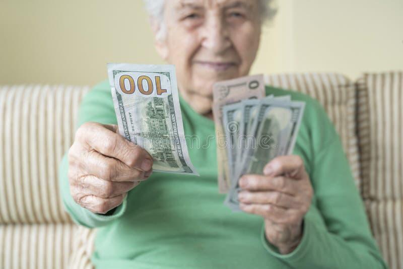 Una donna anziana che regge e dà dollari americani immagine stock
