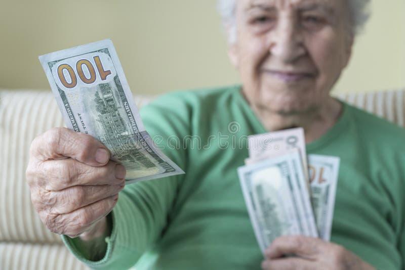 Una donna anziana che regge e dà dollari americani immagini stock