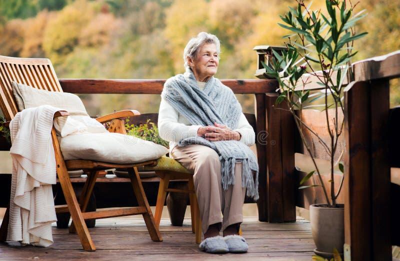 Una donna anziana che si siede all'aperto su un terrazzo un giorno soleggiato in autunno immagini stock