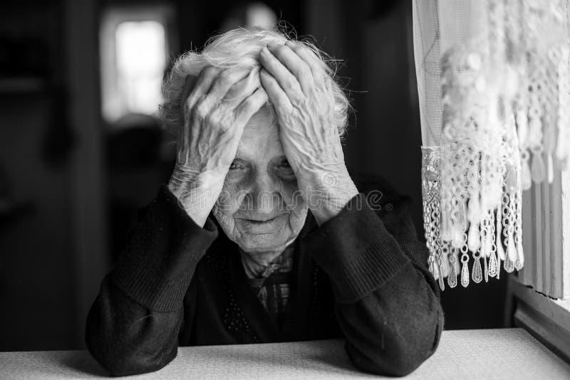 Una donna anziana che si siede alla tavola in uno stato depresso fotografie stock