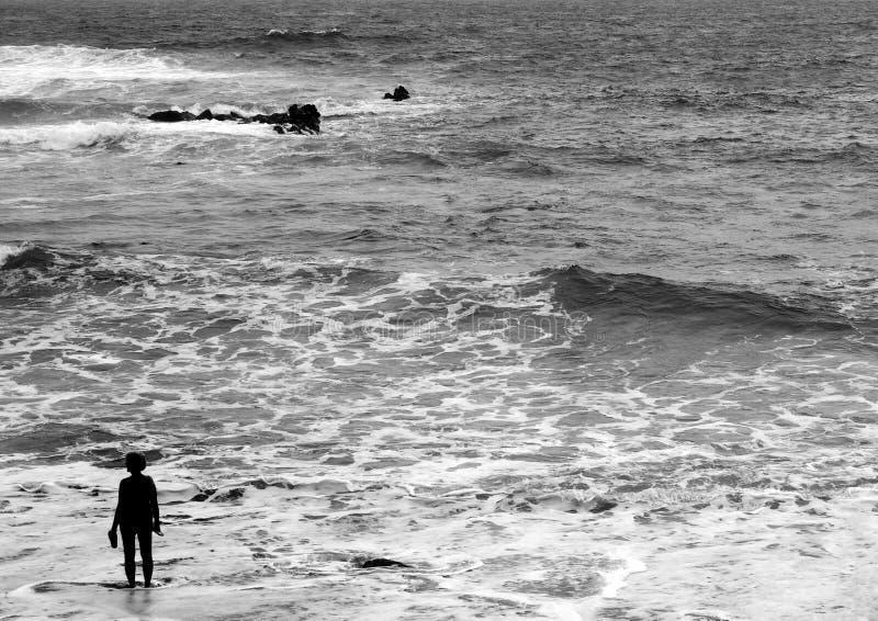 Una donna anziana che sta da solo nel mare nella sera con le onde fotografia stock libera da diritti