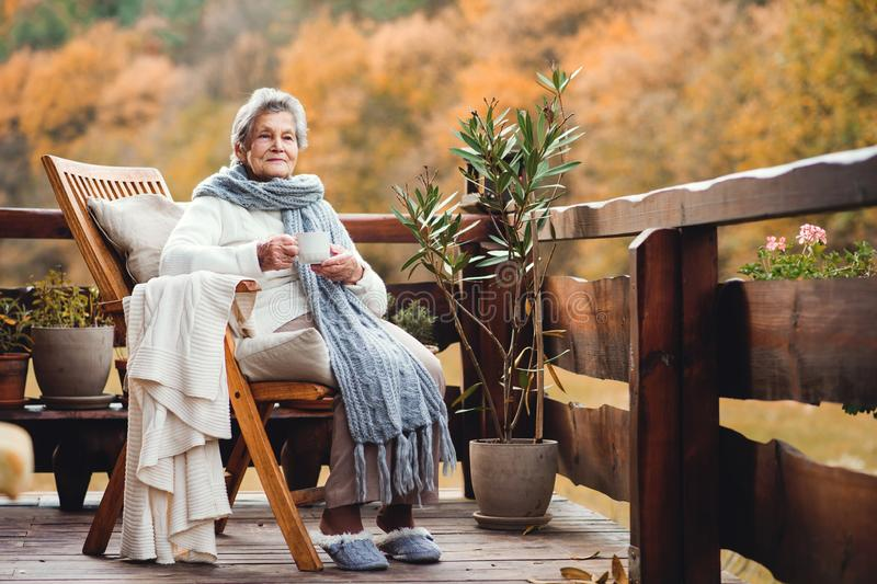 Una donna anziana con una tazza che si siede all'aperto su un terrazzo un giorno soleggiato in autunno fotografia stock