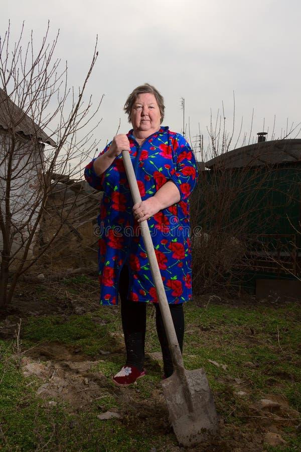 Una donna anziana con una pala fotografie stock libere da diritti