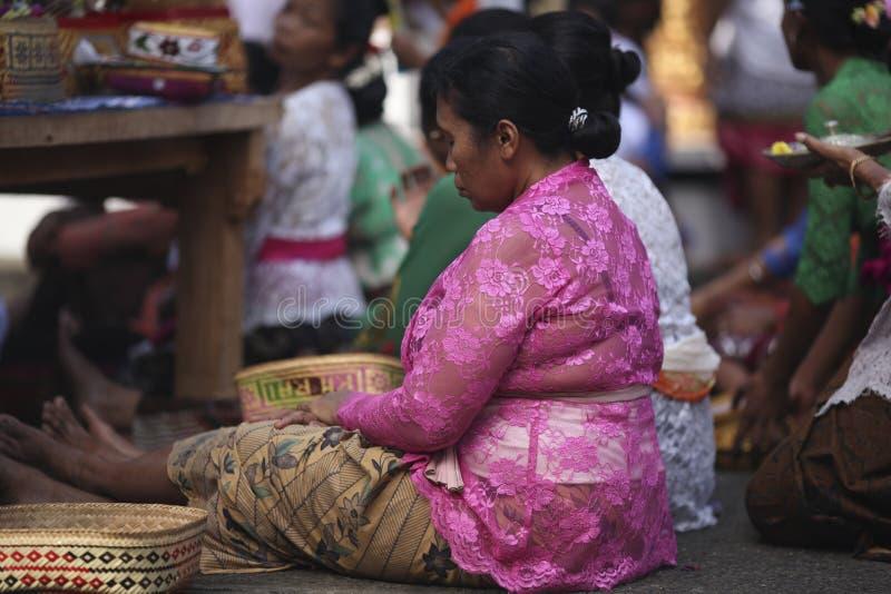 Una donna anziana di balinese che prega in vestiti tradizionali su cerimonia del tempio indù, isola di Bali, Indonesia fotografie stock libere da diritti