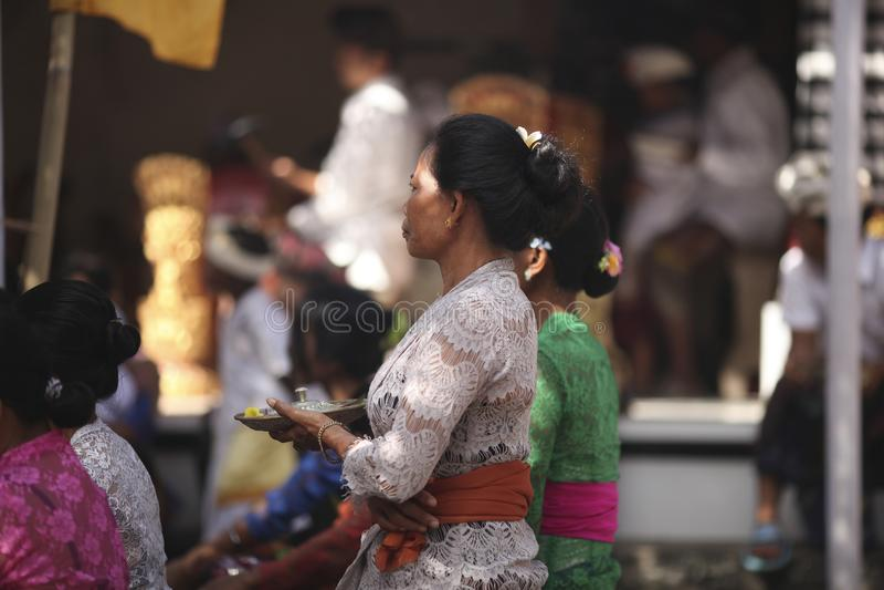 Una donna anziana di balinese in vestiti tradizionali su cerimonia del tempio indù, isola di Bali, Indonesia fotografia stock libera da diritti