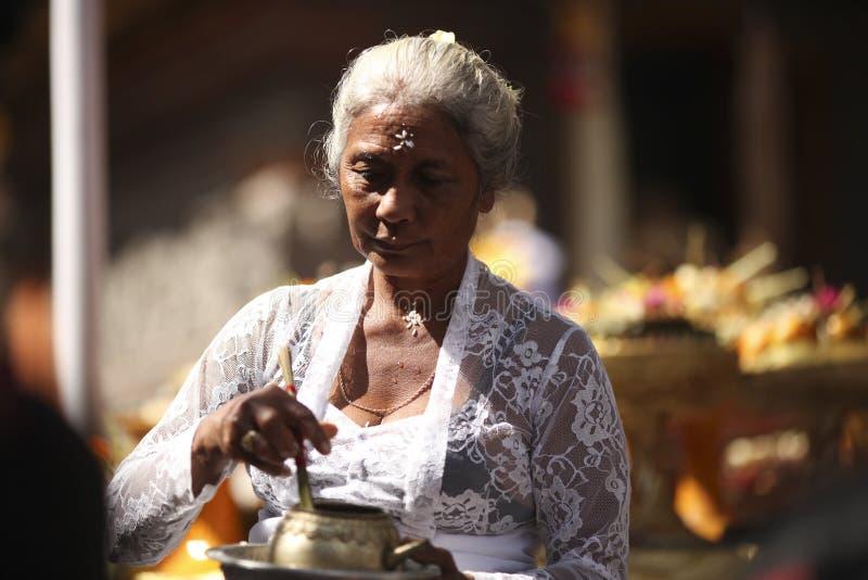 Una donna anziana di balinese in vestiti tradizionali su cerimonia del tempio indù, isola di Bali, Indonesia fotografia stock
