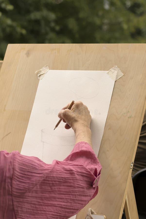 Una donna anziana impara assorbire uno studio di arte fotografie stock