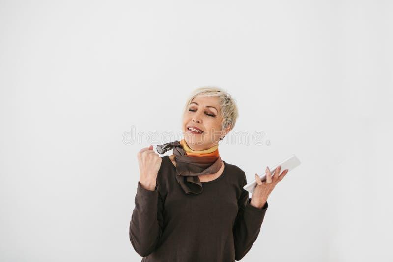 Una donna anziana moderna positiva tiene una compressa in sue mani e la usa Il gesto mostra la parola sì, il positivo e fotografia stock libera da diritti