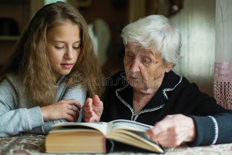 Una donna anziana - una nonna con una bambina - nipote che legge un libro famiglia immagine stock libera da diritti