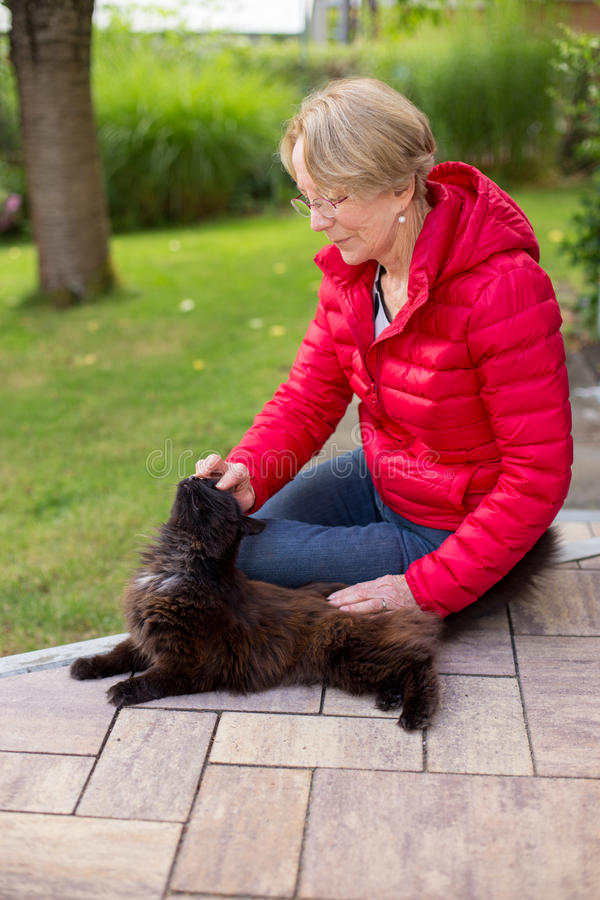 Una donna anziana piacevole segna appassionato il suo gatto fotografie stock libere da diritti
