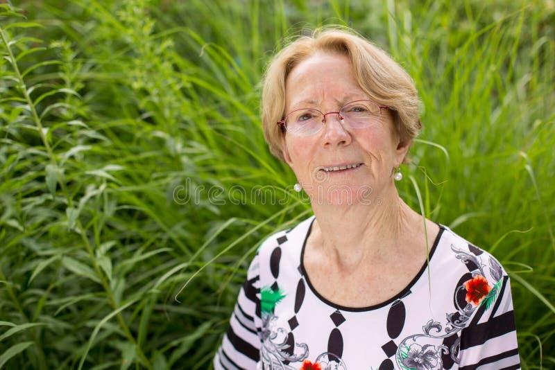 Una donna anziana piacevole sta sognando in un bello giardino immagine stock