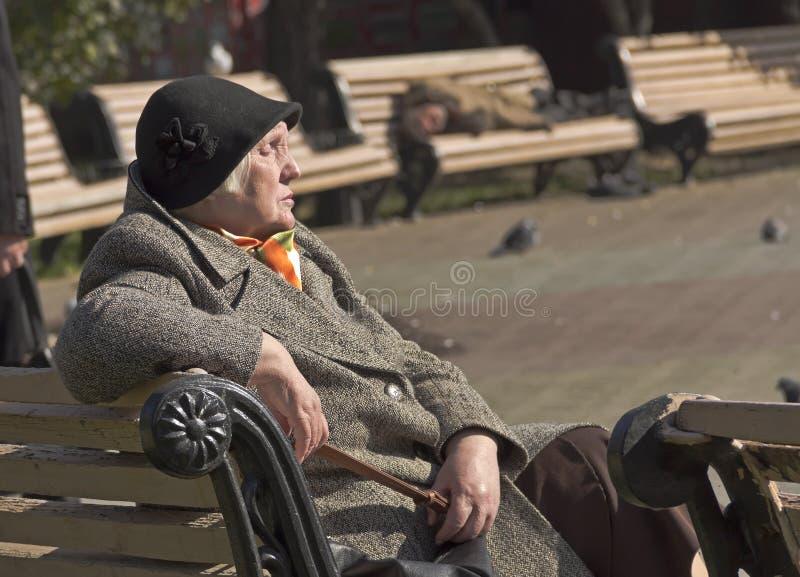 Una donna anziana si siede su un banco con i suoi occhi chiusi, prendendo il sole nell'ambito dei raggi del sole di autunno immagini stock libere da diritti