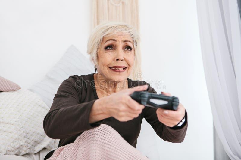 Una donna anziana sta giocando un video gioco Persona anziana e tecnologia moderna fotografie stock libere da diritti