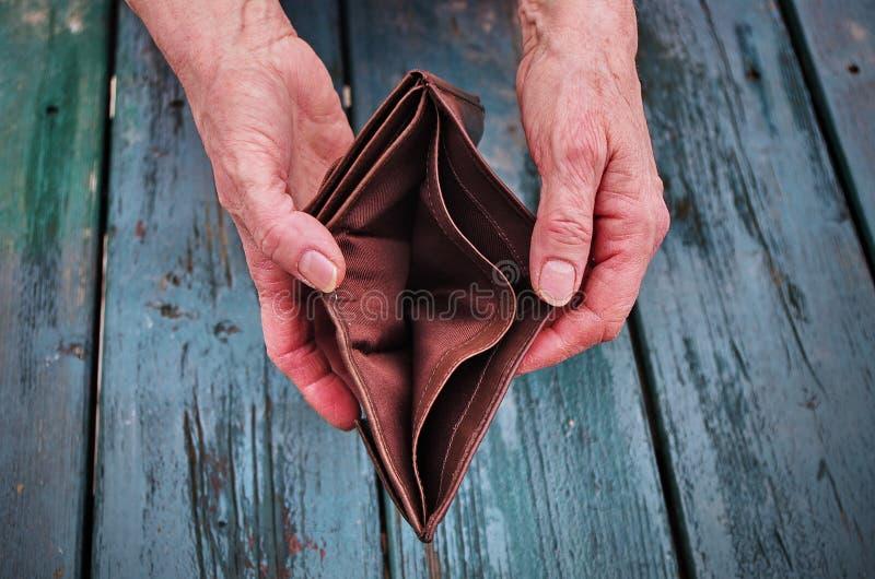 Una donna anziana tiene una borsa vuota sulla tavola d'annata di legno Il concetto di povertà nel pensionamento Povertà estrema g immagini stock libere da diritti