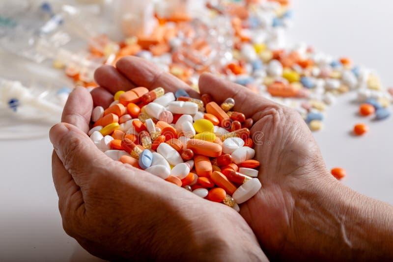 Una donna anziana tiene i lotti delle pillole colorate in mani su un fondo bianco fotografia stock libera da diritti