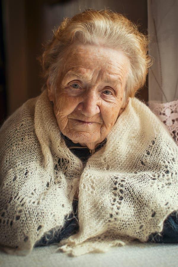 Una donna anziana, un ritratto che si siede alla tavola fotografia stock libera da diritti