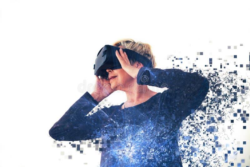 Una donna anziana in vetri di realtà virtuale è sparsa dai pixel Fotografia concettuale con gli effetti visivi con fotografie stock