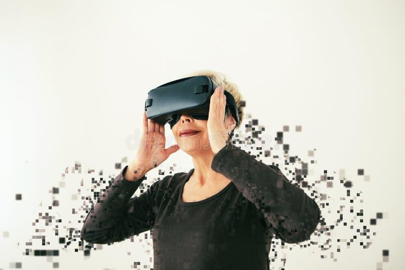 Una donna anziana in vetri di realtà virtuale è sparsa dai pixel Fotografia concettuale con gli effetti visivi con fotografia stock libera da diritti