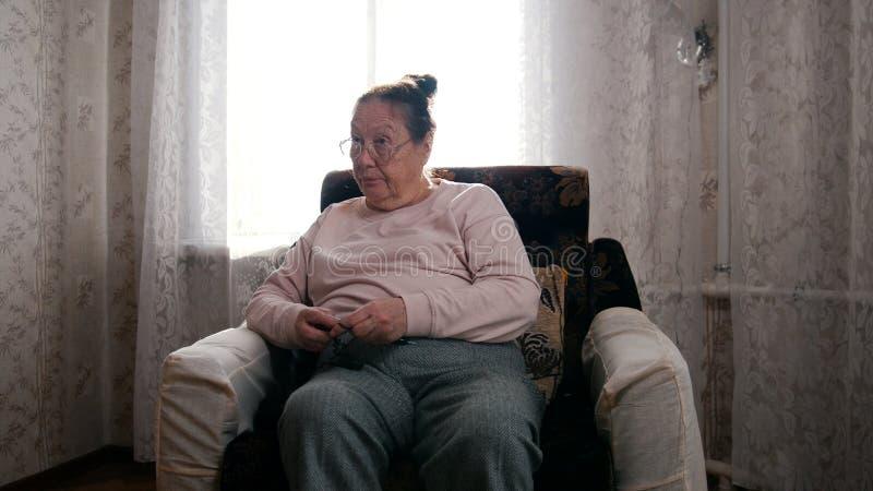 Una donna anziana in vetri e maglione rosa che si siedono nella poltrona e nel tricottare immagine stock