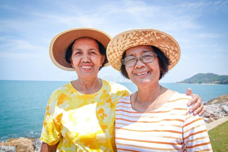 Una donna asiatica anziana che viaggia al mare fotografia stock