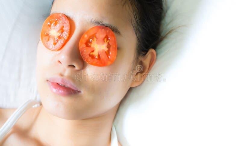 Una donna asiatica ha messo i pezzi di pomodoro sui suoi occhi fotografia stock