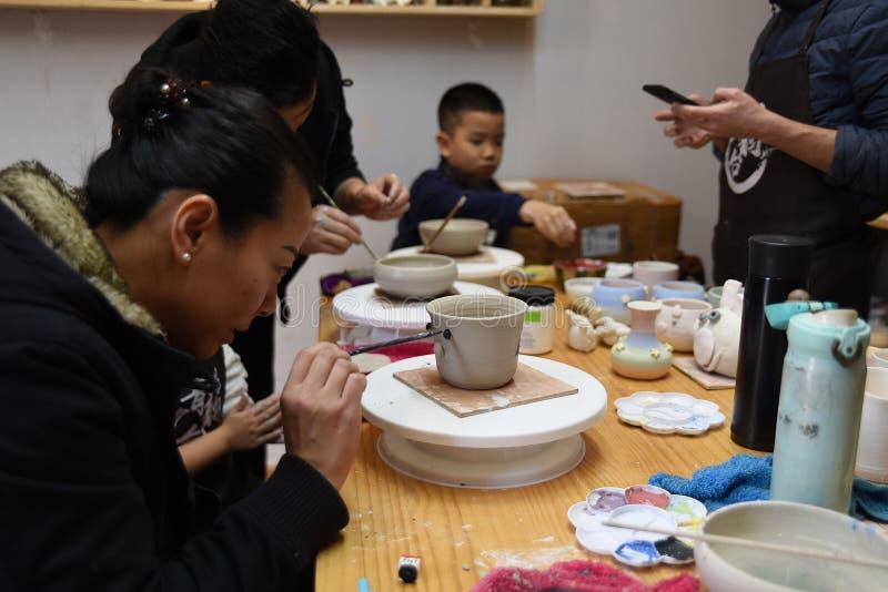 Una donna asiatica sta concentrandosi sulla fabbricazione delle terraglie fotografia stock libera da diritti