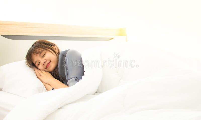 Una donna asiatica sta dormendo sul suo letto immagini stock libere da diritti