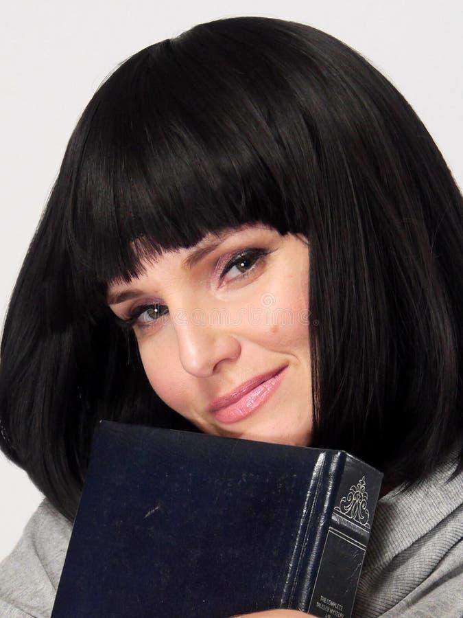 Una donna attraente sta posando con un libro contro un fondo bianco immagini stock