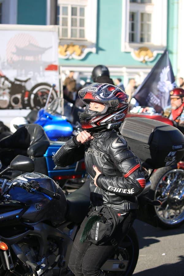 Una donna in attrezzatura piena del motociclista si fissa davanti ad uno specchio del motociclo immagine stock