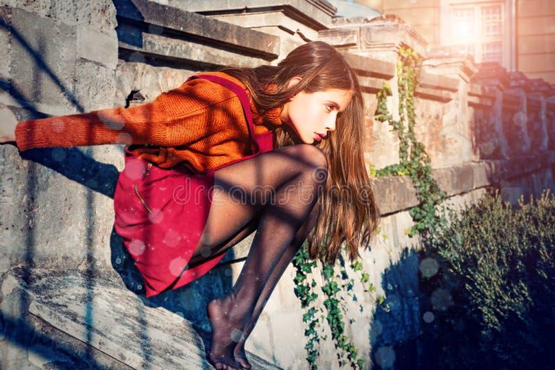 Una donna autunnale in gonna e calze si siedono dietro le scale architettura Concetto di moda Modella giovanile Godere fotografie stock