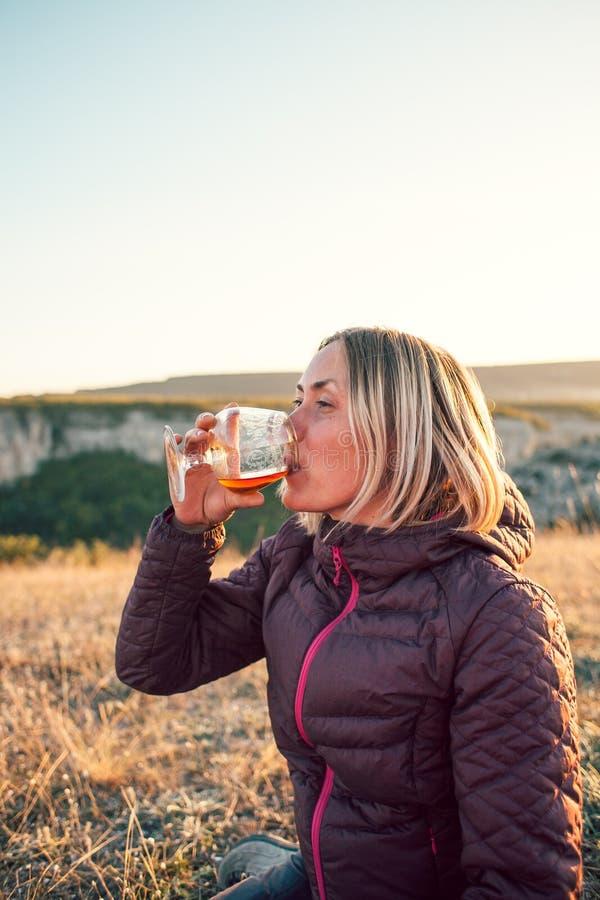 Una donna beve da un vetro immagini stock