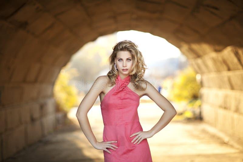 Una donna bionda alta con il vestito di corallo dalla capezza in tunnel luminoso fotografia stock