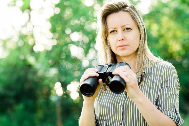 Una donna bionda con il binocolo nero resta all'aperto fotografia stock