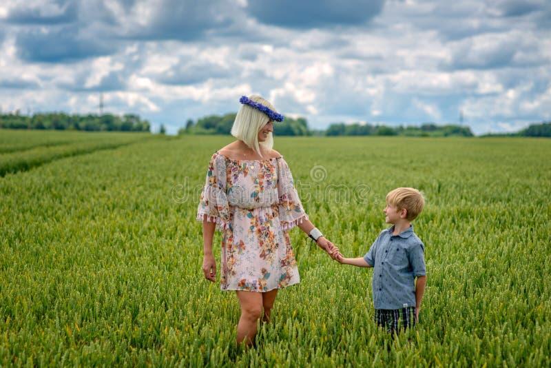 Una donna bionda con un bambino passa attraverso un campo dei raccolti immagini stock libere da diritti
