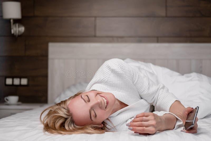 Una donna bionda di mezza età attraente in un abito bianco sta trovandosi su un letto in una camera da letto e sta utilizzando un fotografia stock
