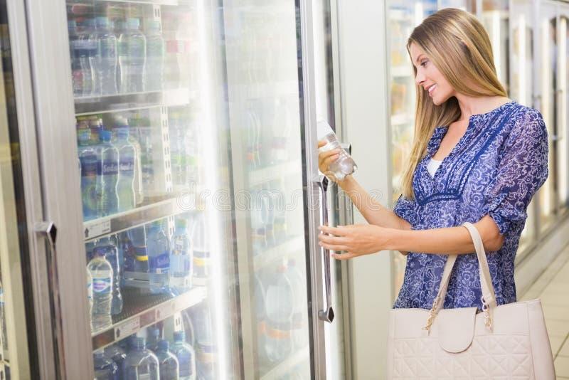 Una donna bionda sorridente graziosa che compra i prodotti congelati immagini stock libere da diritti