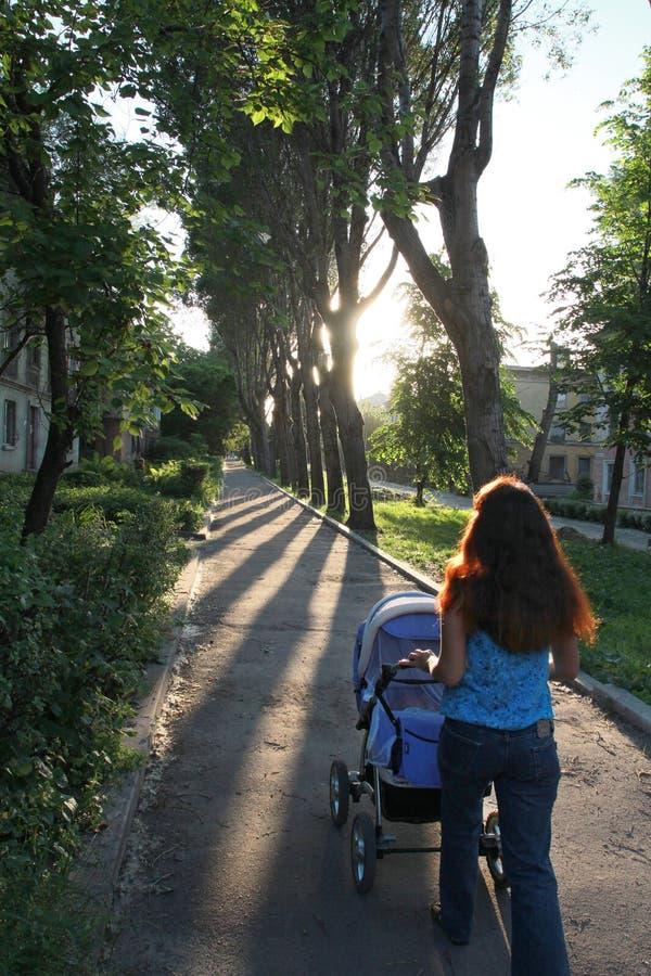 Una donna cammina con un bambino in un passeggiatore fotografie stock