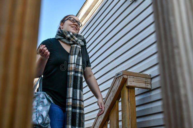 Una donna cammina sui suoi punti del portico anteriore immagini stock libere da diritti