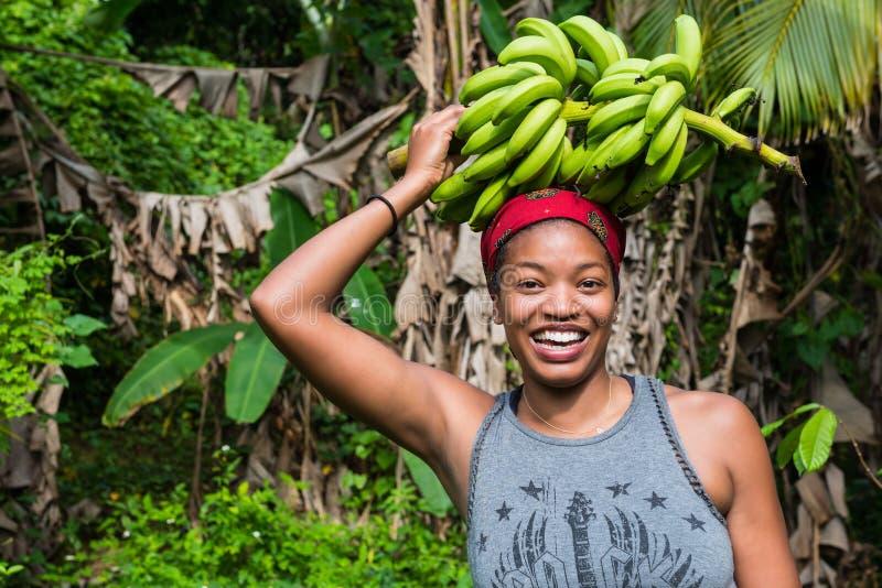 Una donna caraibica sorridente con un mazzo di banane verdi su lei capa immagini stock