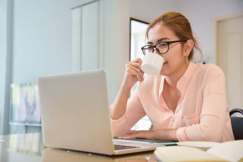 Una donna che fa compera online a casa immagine stock