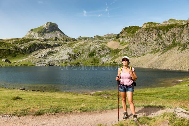Una donna che fa un'escursione vicino ad un lago della montagna immagini stock