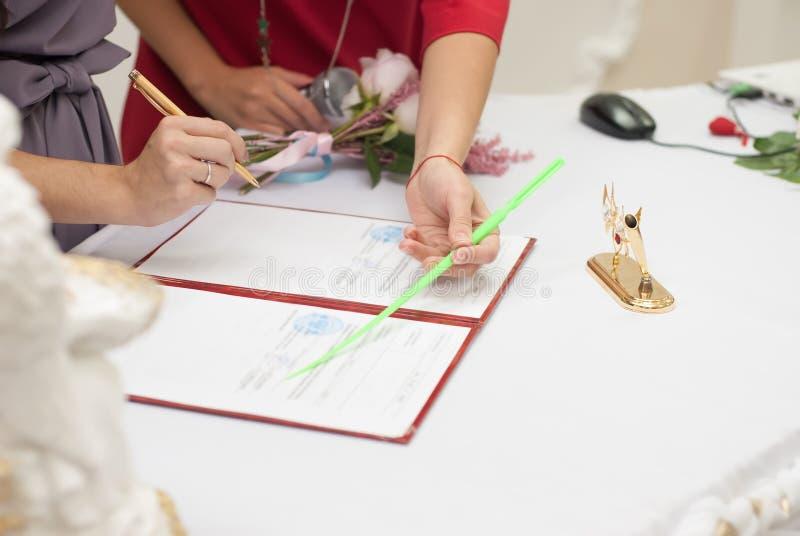 Una donna che firma un contratto di matrimonio, fotografie stock
